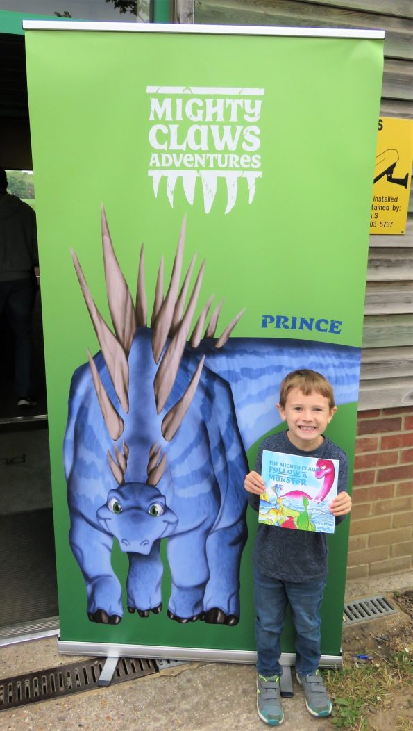 Jake holding the book Mighty Claws whilst stood in front of a sign with a dinosaur