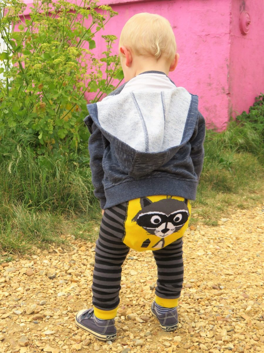 William with his back to us on a gravel path wearing his ricky raccoon leggings