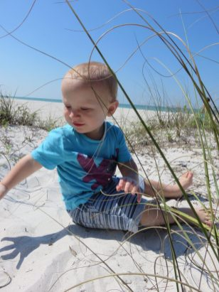 william sat on the sand amongst the long grass