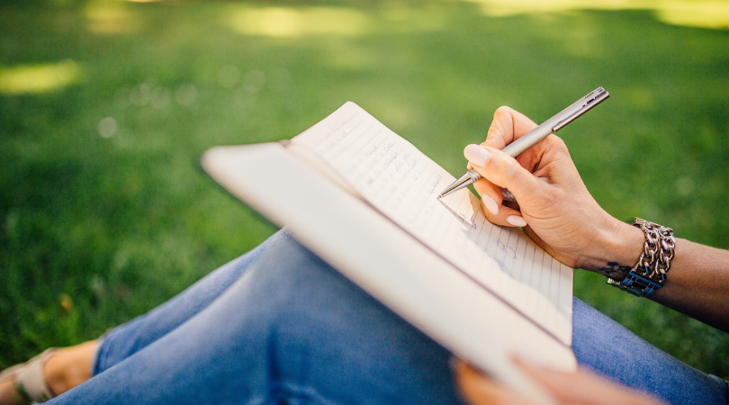 woman writing in a notebook sat outside