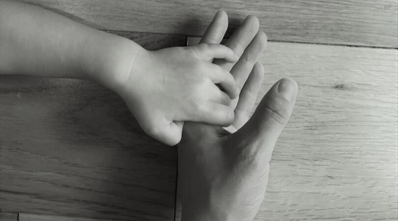 black and white photo of a mum hand holding a toddlers
