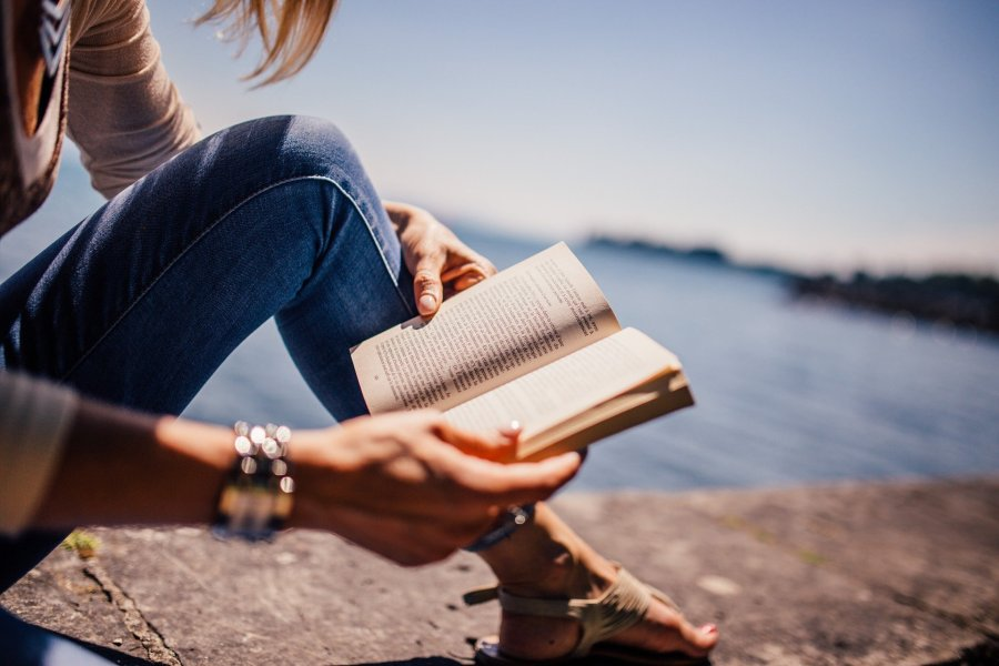 a lady reading a book next to the sea one of the positive new year's resolutions