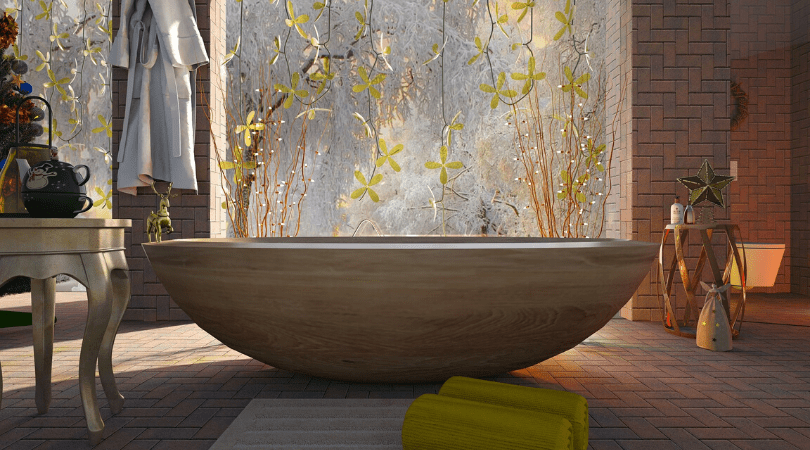stunning bath in middle of a room with a large window and plants