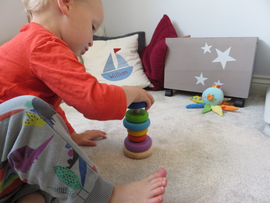 William playing with the plan toys stacker