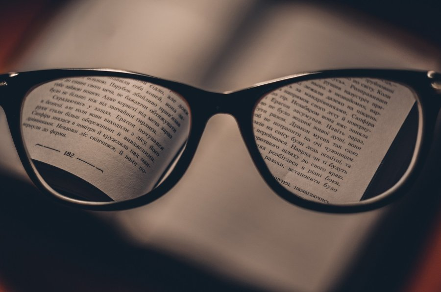 a pair of glasses looking through at a book
