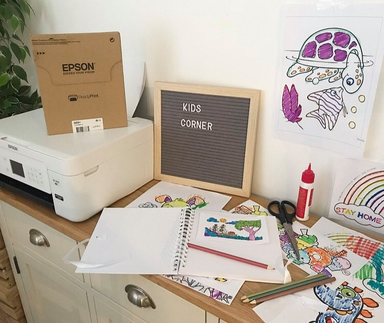 a scrapbook for the colouring in pages with the glue and scissors next to it. The printer is in the photo with the ink box on top