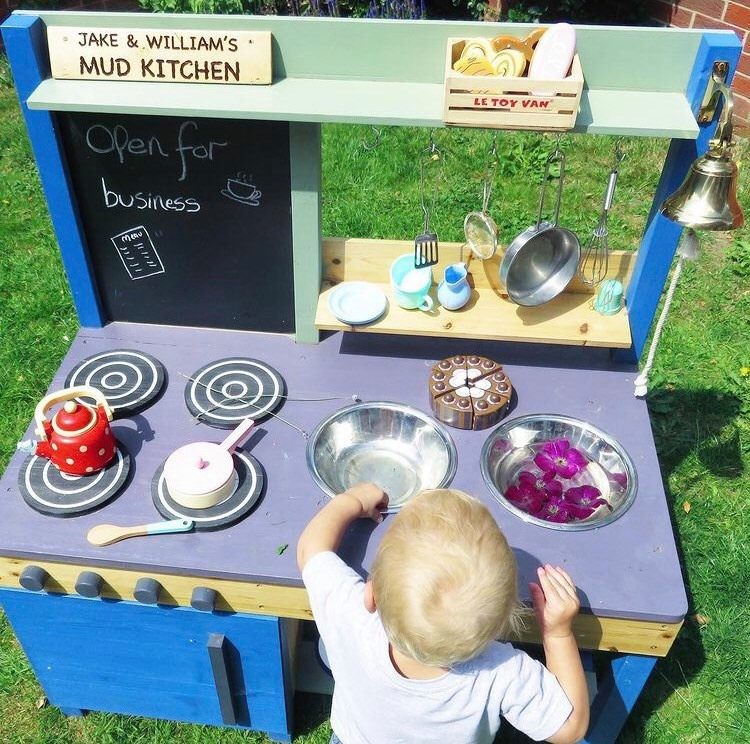 small child playing with a mud kitchen with water and petals