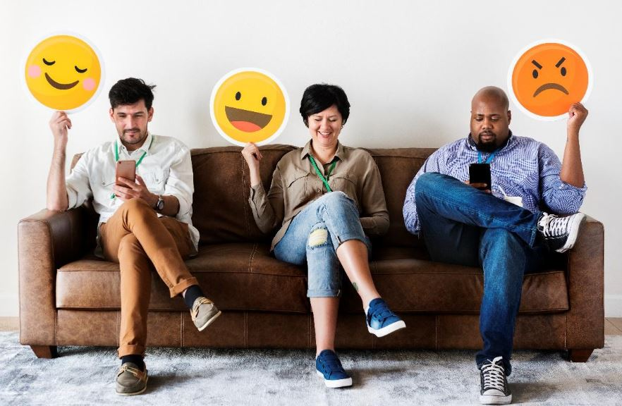 three people on sofa holding emoji signs