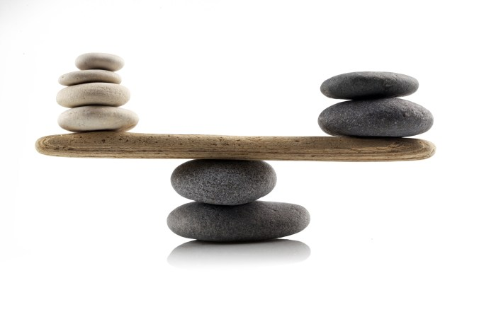 balancing stones on white background indicating a neutral point and tying in to the article them of emotional intelligence is neutral