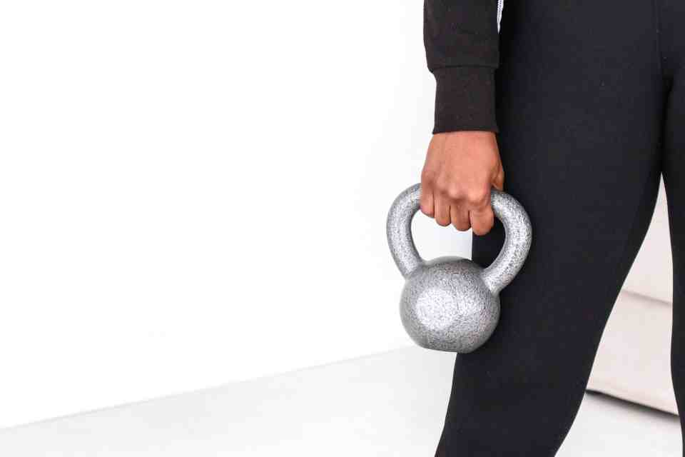 woman holding kettle-bell weight as part of a well-rounded fitness routine.
