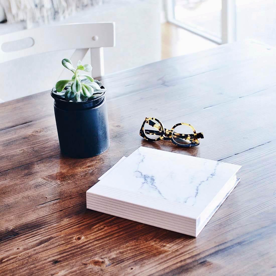 A imagem mostra um vaso de planta, um par de óculos e um livro