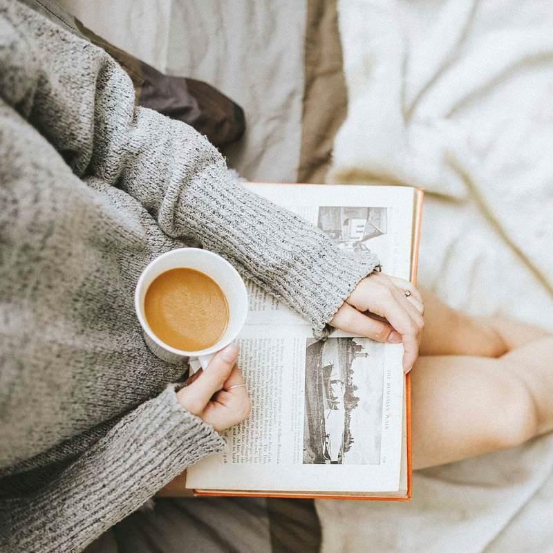 Mulher com xícara na mão e livro