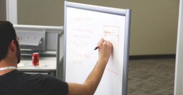 persona escribiendo en una pizarra en contexto de trabajo en equipo