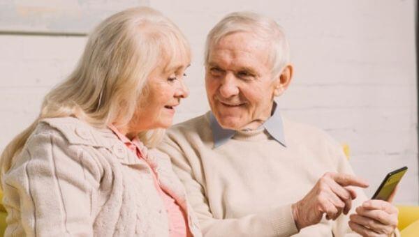 """alt=""""idosos olhando as opções para refinanciamento no celular"""""""