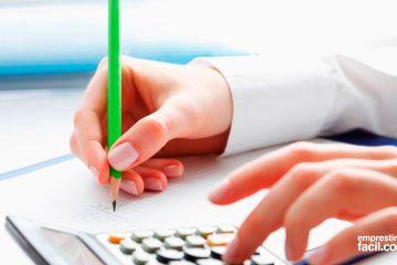 Mãos realizando cálculo das contas de início do ano