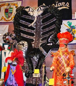 Notice the towering snake headpiece next to the mannequin.