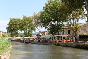 a picture of the port of Trebes is lined with quaint restaurants