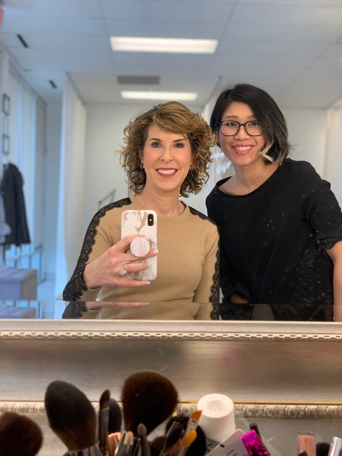 two women posing for selfie in mirror