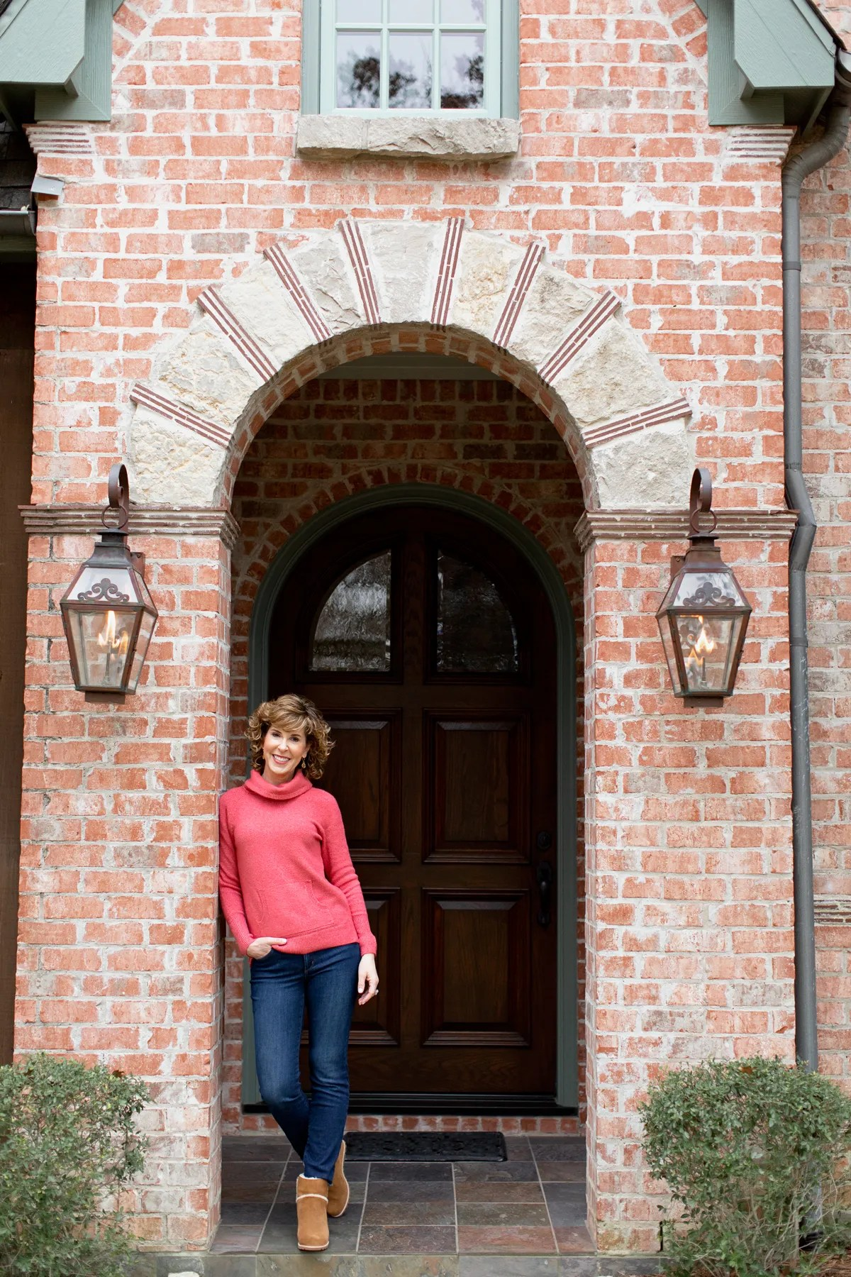 woman in coral turtleneck in arched entry