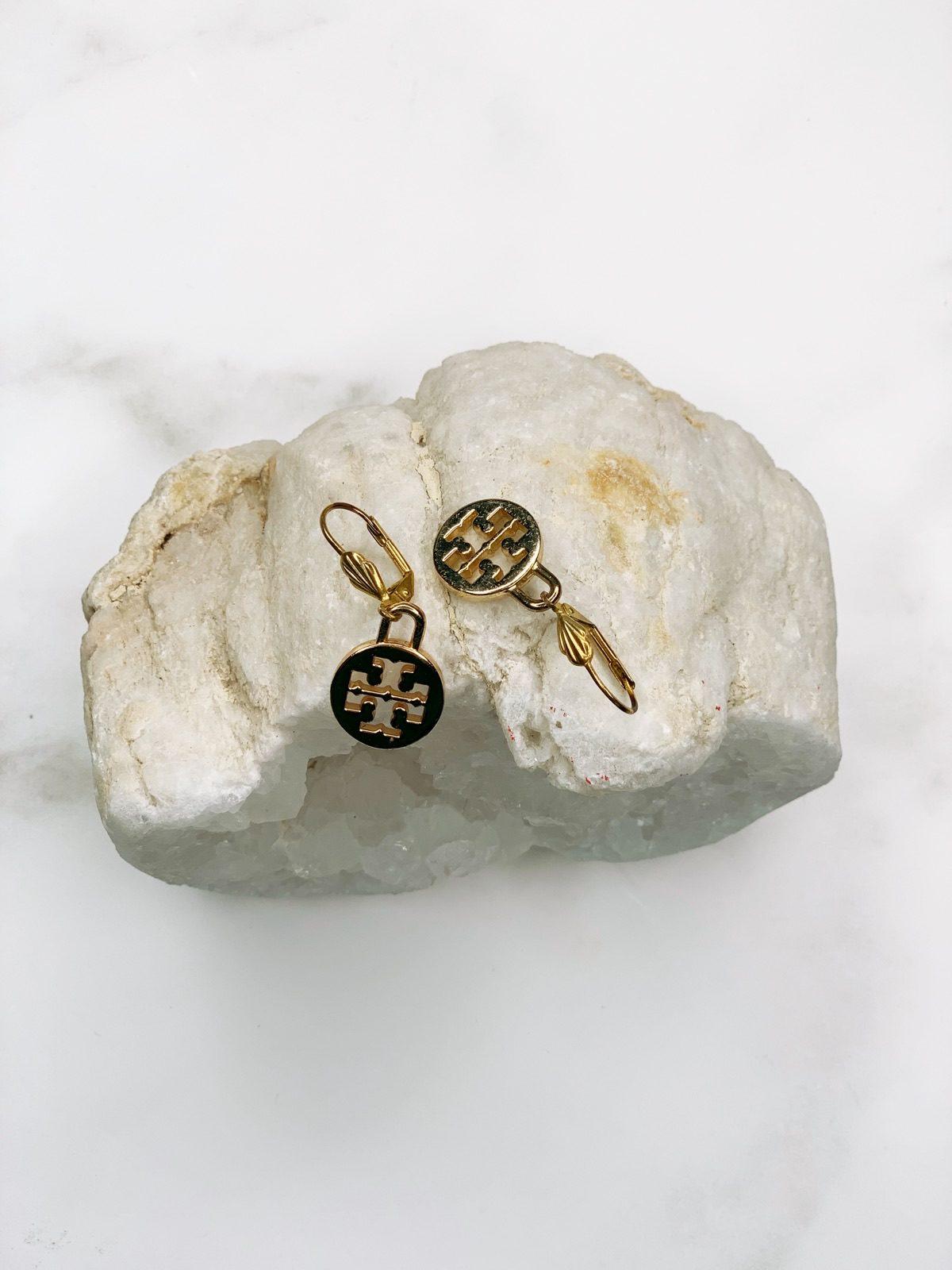 gold tory burch earrings on white rock