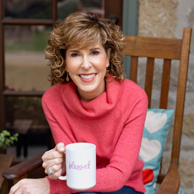 woman over 50 wearing coral turtleneck sweater holding coffee cup that says blessed