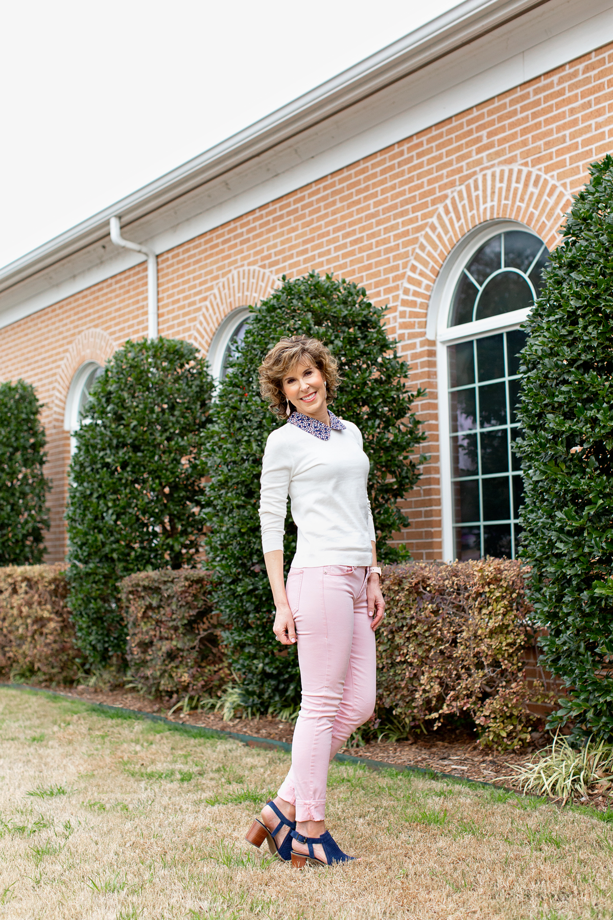 woman wearing pink pants and white sweater with blue collar looking over her shoulder