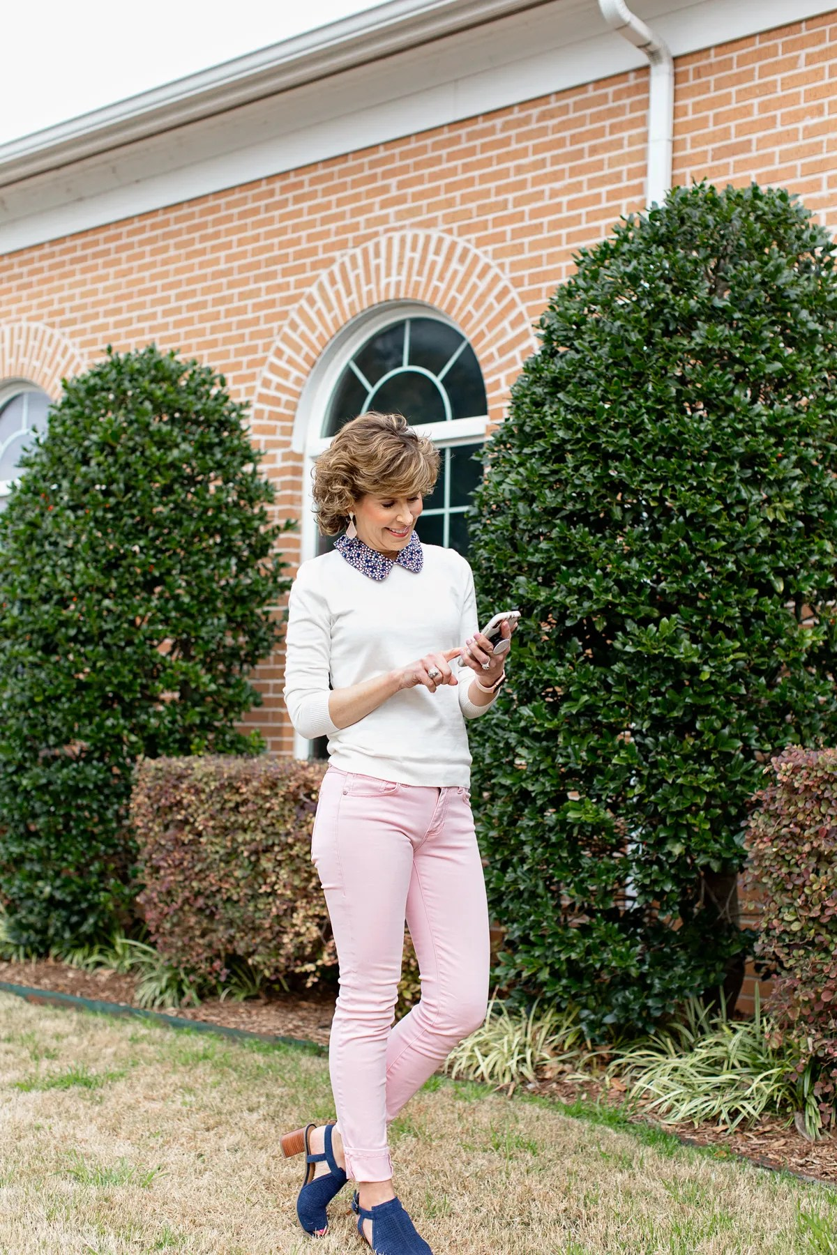 woman in white top and pink pants looking at phone