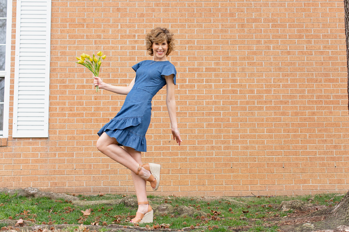woman in blue dress balancing on one leg and holding daffodils