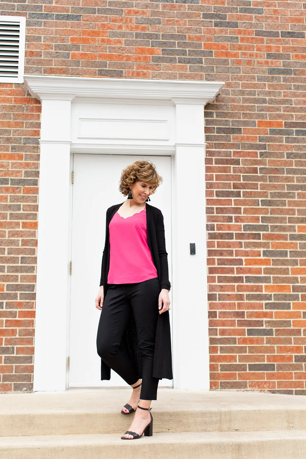 woman standing in front of doorway in pink top with black sweater