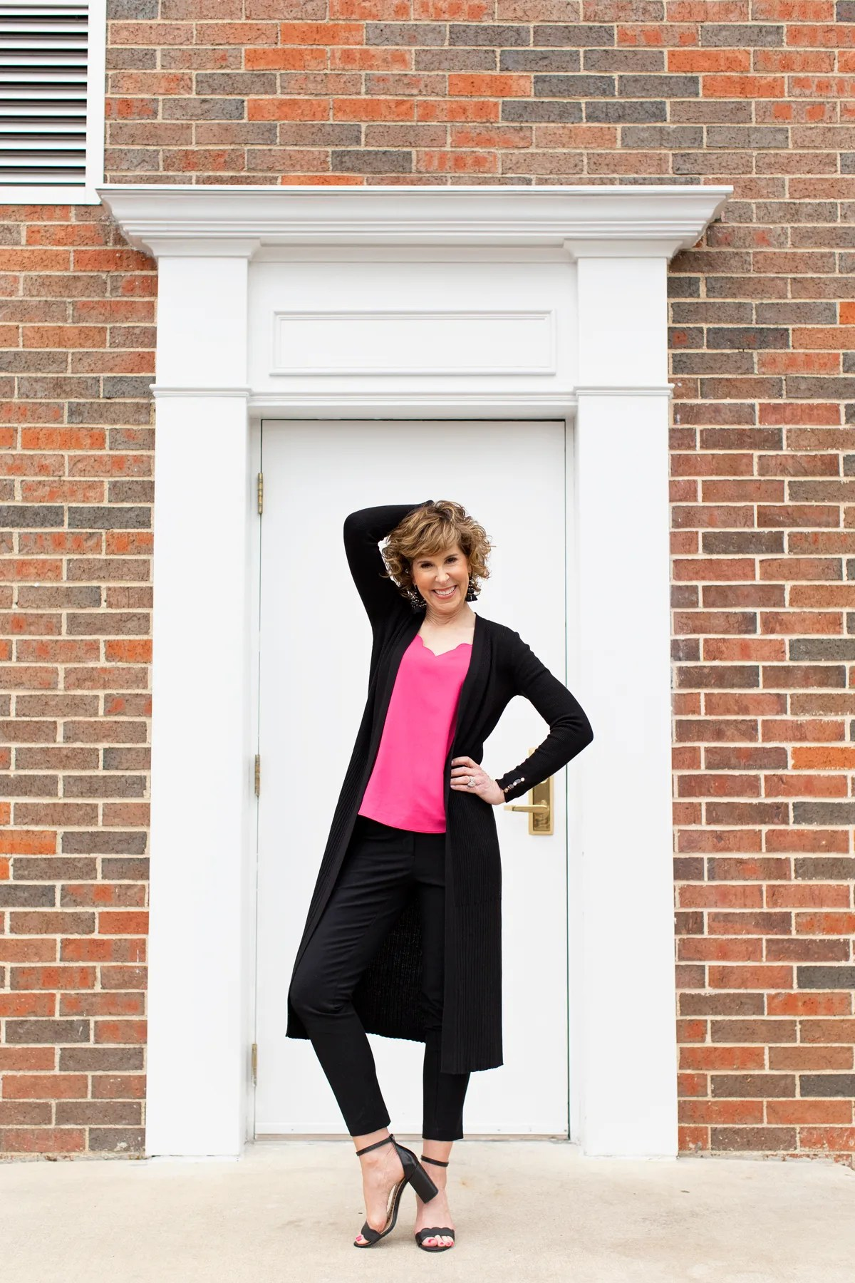 woman standing in front of doorway in pink top with black sweater