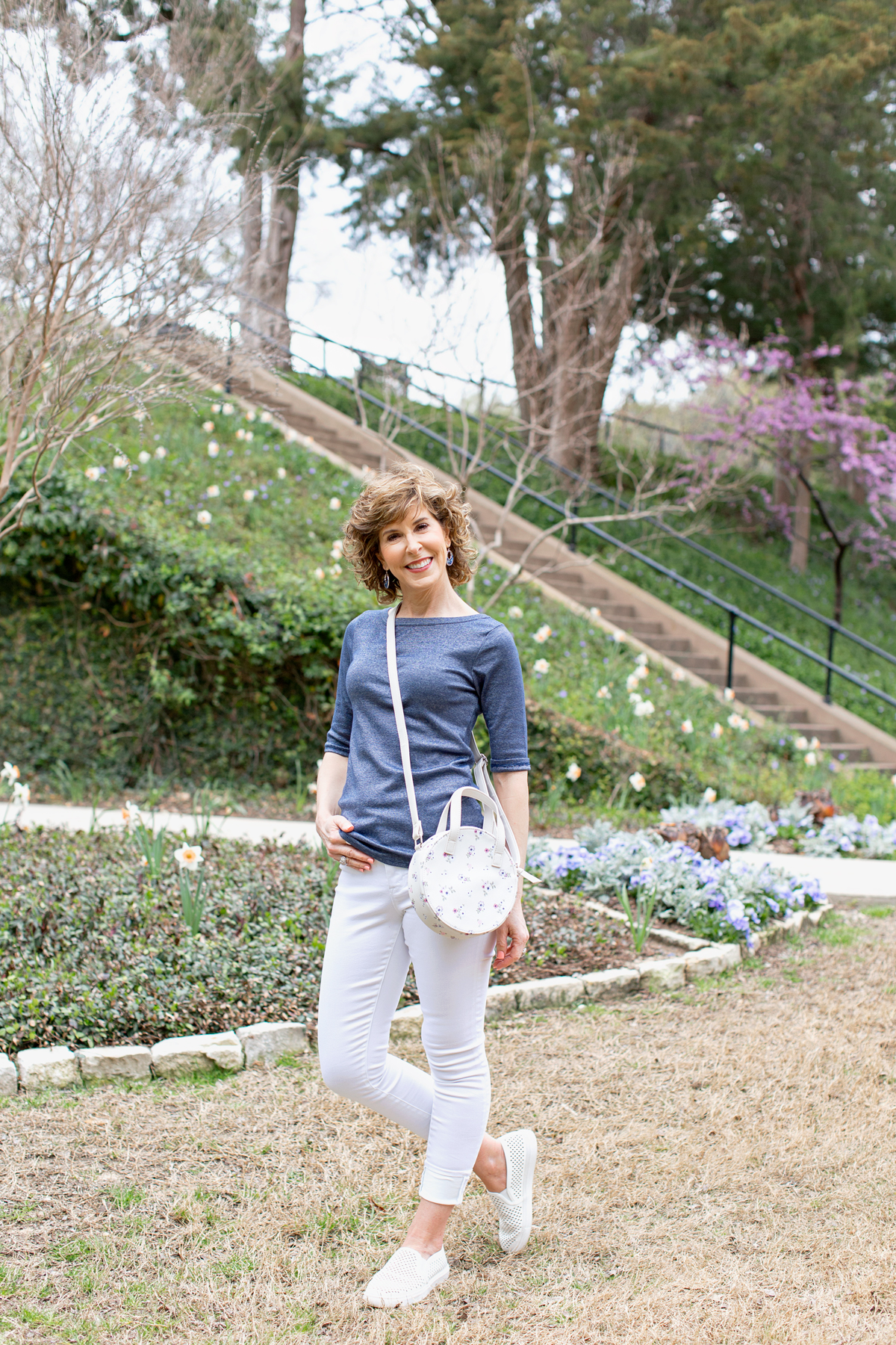 woman in blue tee and white jeans in park looking at camera