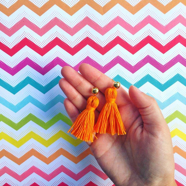 hand holding orange tassel earrings against colorful background
