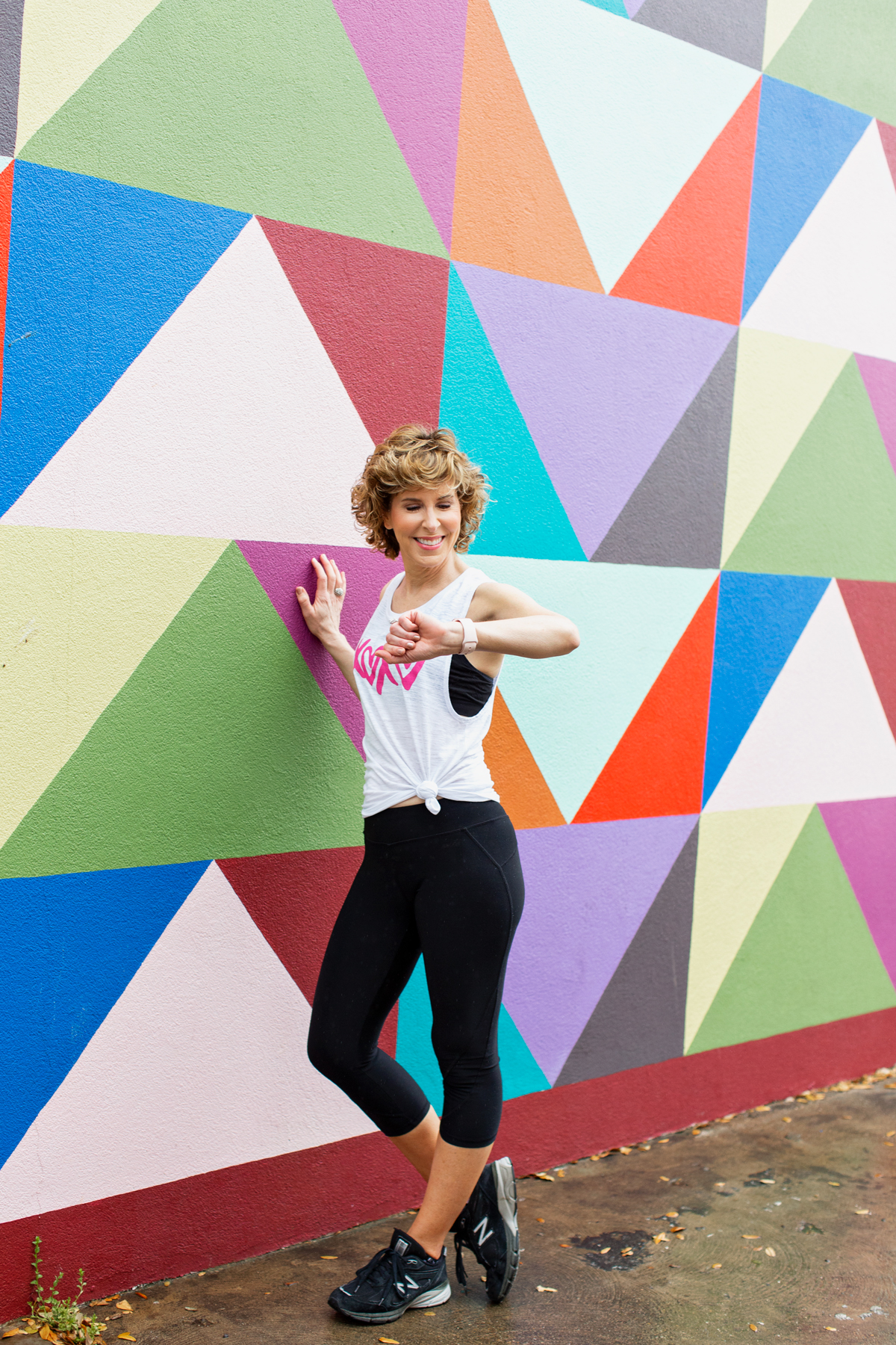 woman standing by colorful wall looking at her watch