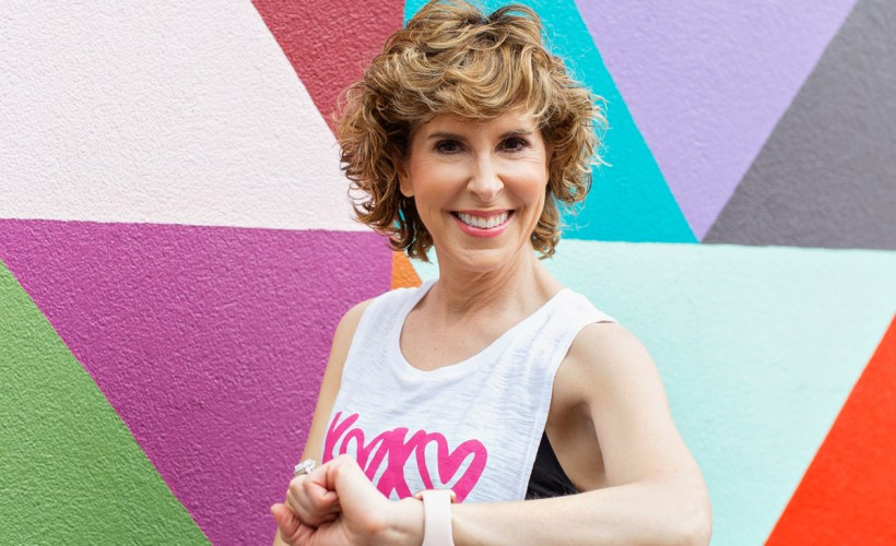 woman wearing activewear standing by colorful wall looking at camera