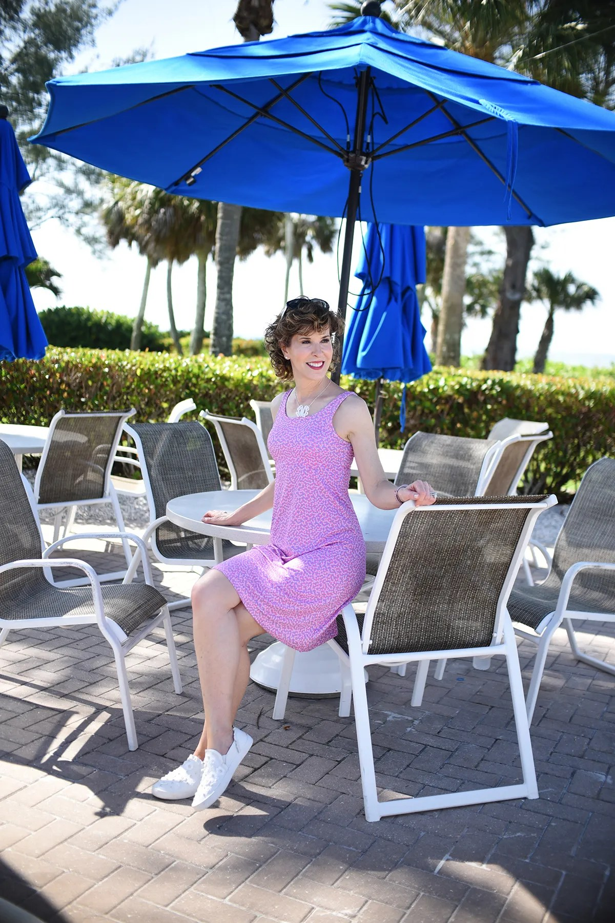 woman wearing pink dress sitting on arm of chair at table with blue umbrella