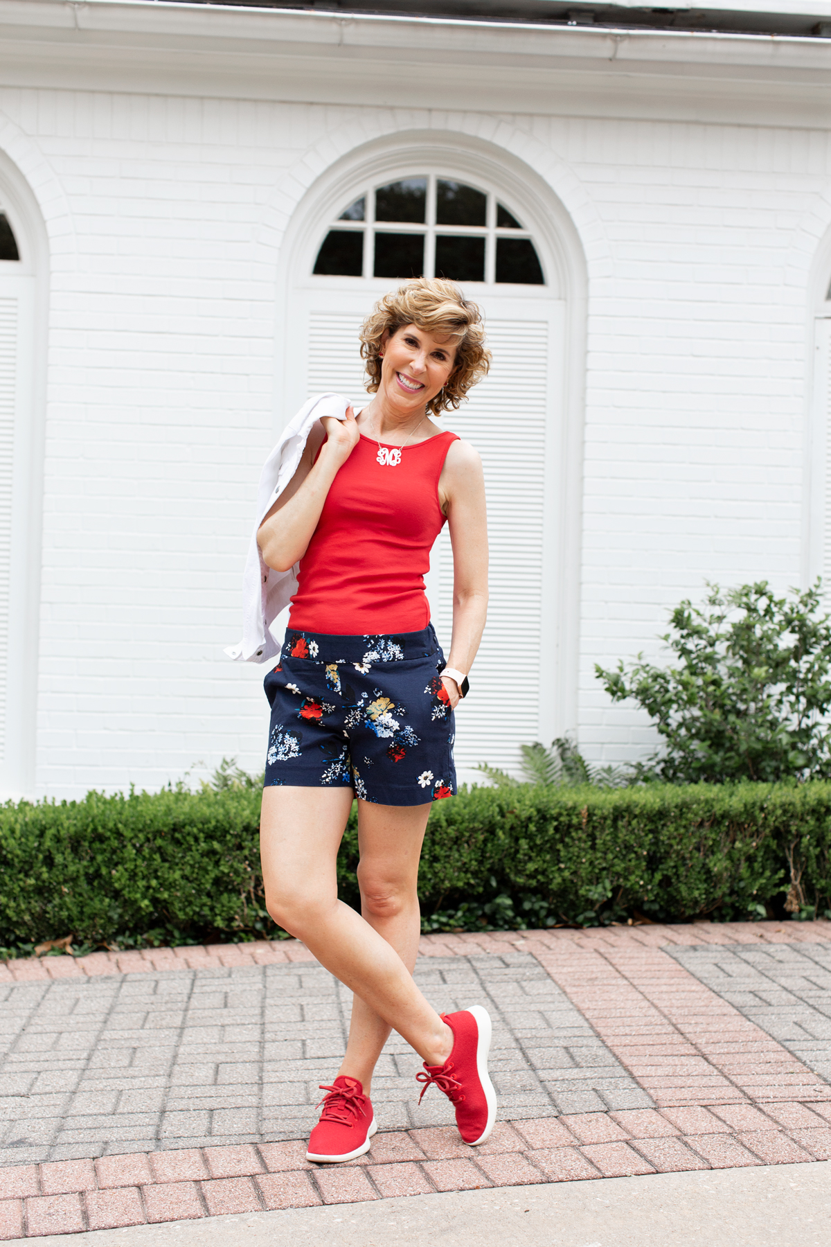 woman wearing red white and blue july 4th look in front of a white house