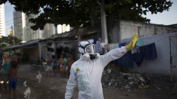 A municipal worker gestures during an operation to combat the Aedes aegypti mosquitoes that transmits the Zika virus in Recife, Pernambuco state, Brazil, Tuesday, Jan. 26, 2016. Brazil's health minister Marcelo Castro said that nearly 220,000 members of Brazil's Armed Forces would go door-to-door to help in mosquito eradication efforts ahead of the country's Carnival celebrations. (AP Photo/Felipe Dana)
