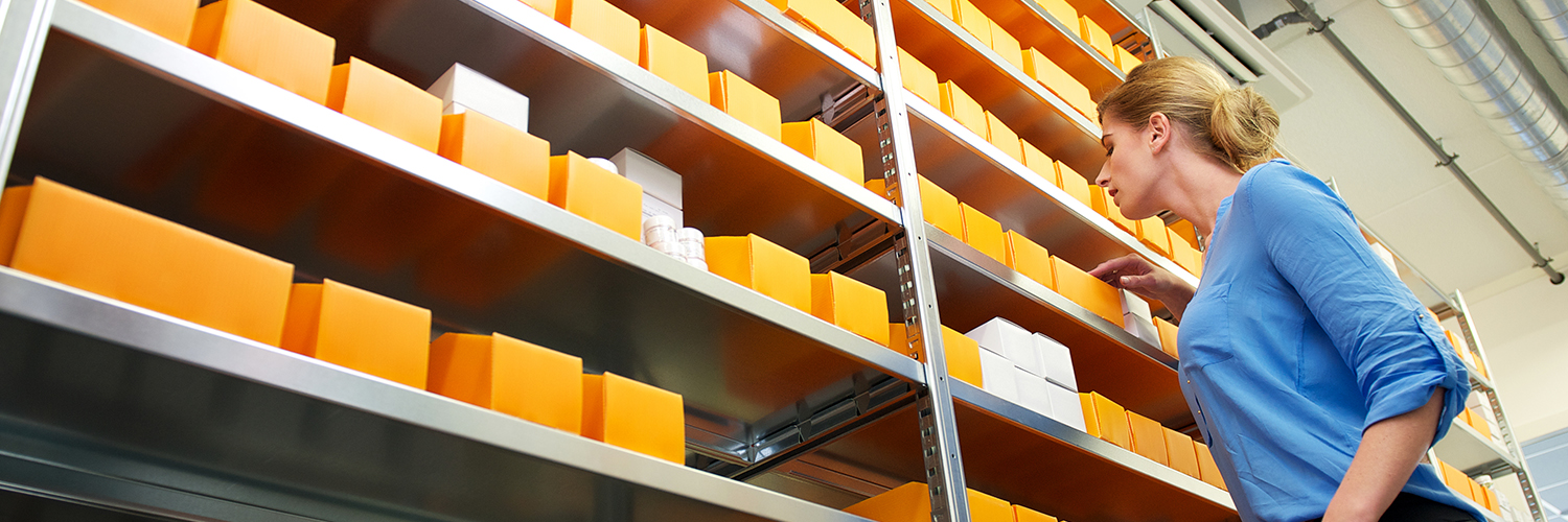 Image of Portrait of person searching shelves for product represents our services.