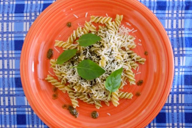 O queijo parmesão ralado e folhinhas de manjericão finalizam o prato