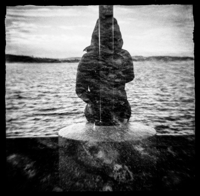 Double exposure of a girl looking a the sea, in Oslo.