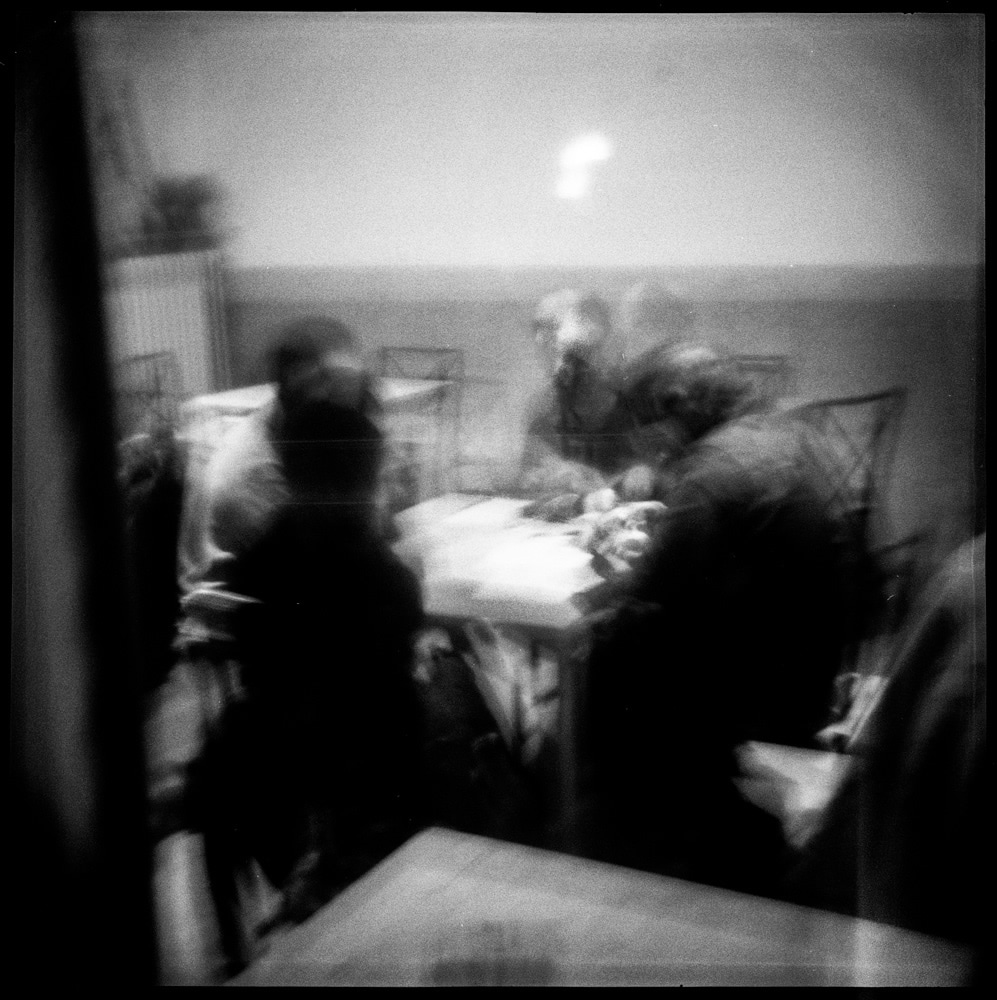 Four men playing cards in a bar, in Italy. Shot through the window.