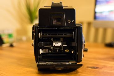 """Mamiya 645 1000S - Loading film step 2 - Squeeze the buttons on both sides of """"120"""" label, then pull out cassette."""