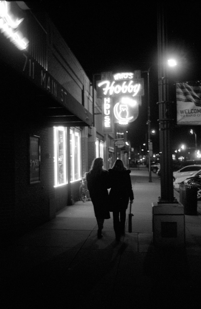 Rapid City Nightwalk - A couple of friends walk down a downtown street at night, Rapid City SD, May 2017 (Leica M2, 35mm Summilux, ILFORD HP5 Plus) - Kenneth Wajda Photographer