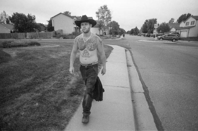 Suburban cowboy - A shirtless man walks in a neighborhood in Longmont Colorado, August 2017 (Nikon F100, 20mm, ILFORD HP5 Plus) - Kenneth Wajda Photographer