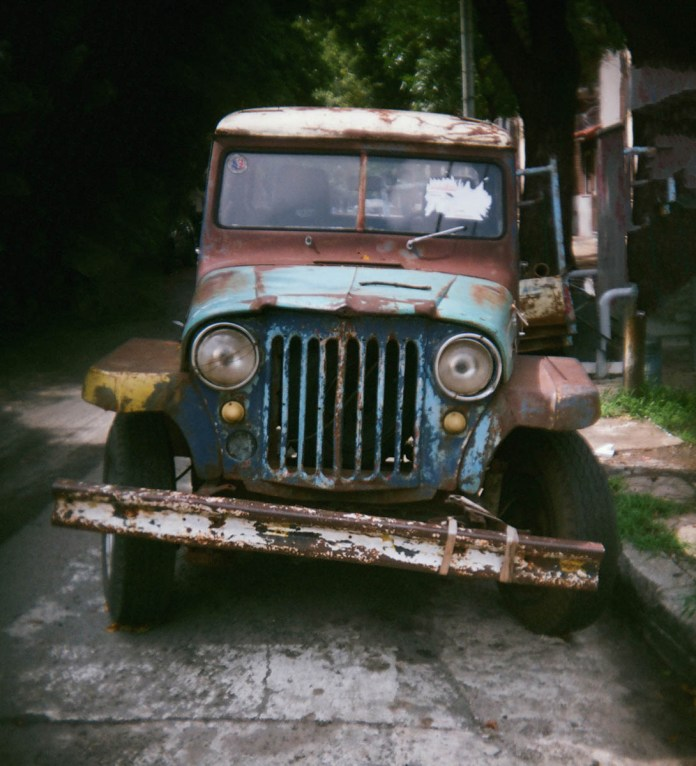 "An old Jeep-imitation vehicle (known as an ""Estanciera"") parked in a neighborhood street in Buenos Aires. Holga 135BC slightly cropped, Lomo 400 negative film."