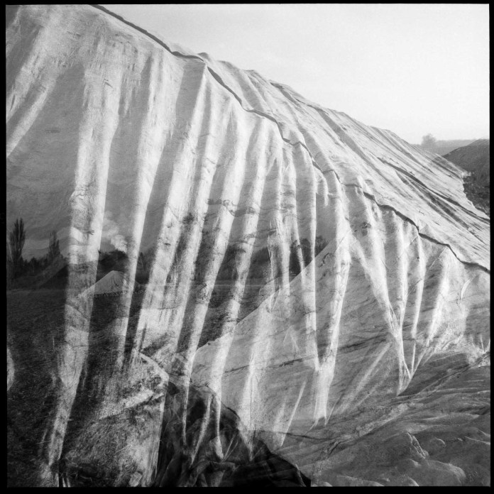 Intentional double exposure featuring tarpaulin covers and landscape, shot on Ilford Pan F, HC110 solution E