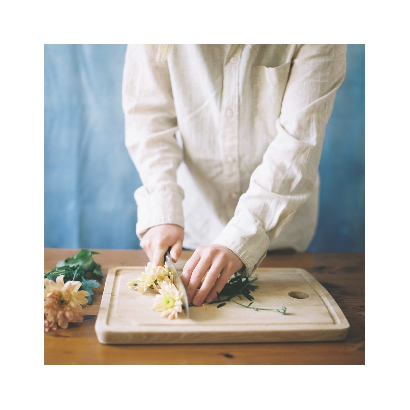 A person chopping the heads off flowers on a chopping board