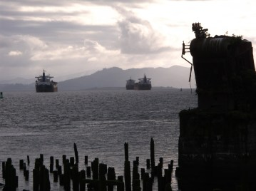 Freighters parked on the Columbia River with old pylons and a boiler from a long gone factory in the foreground