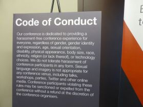 black sign with white letters detailing conference code of conduct