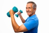 A happy senior man holding up two dumbbells looking confident.